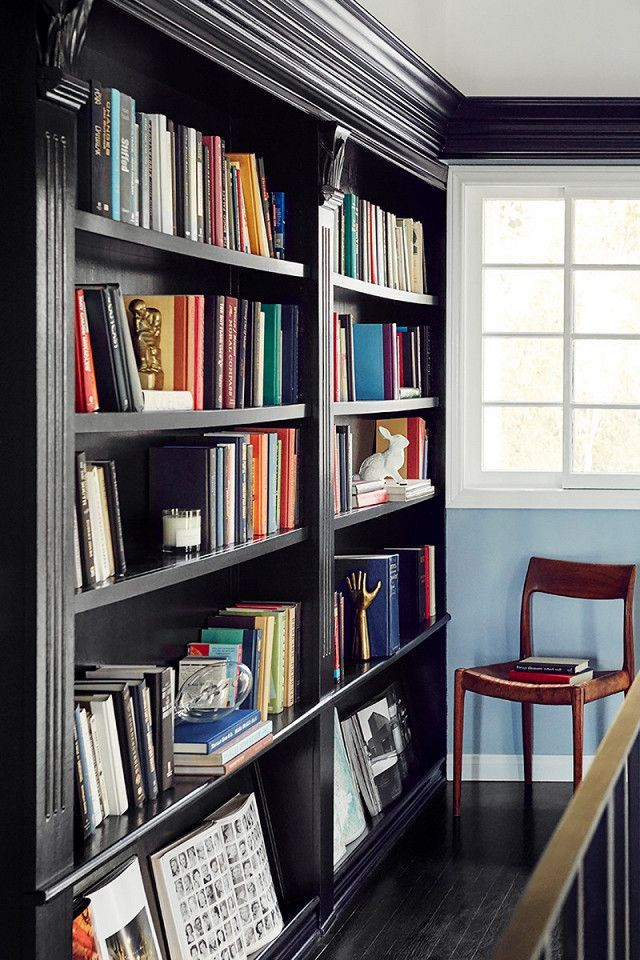 A black bookshelf is a great trick to make colorful books pop. In this home libr…