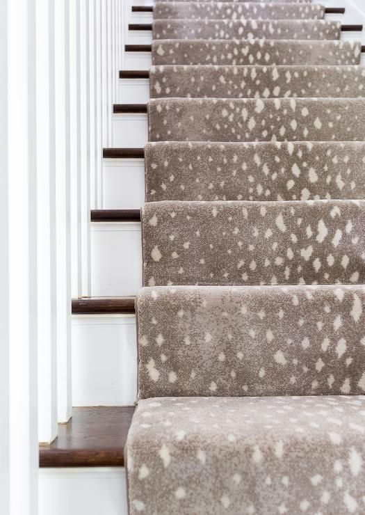 A gray animal print stair runner accents a white staircase boasting stained wood…