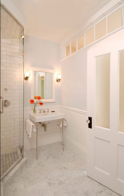 Add windows to a windowless bathroom, even if they're not to the outside world.
