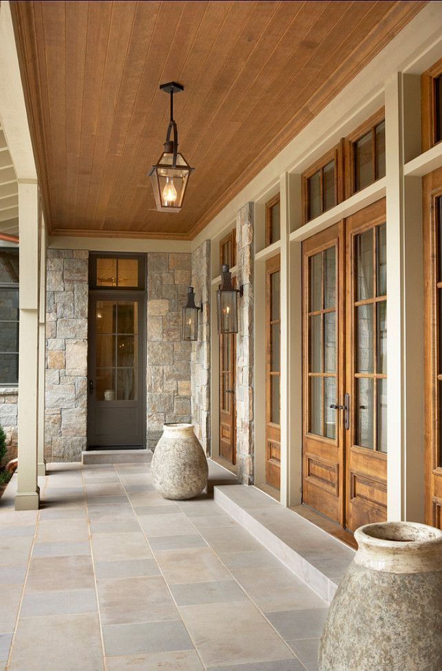 Beautiful covered porch with wood ceiling and stone flooring.