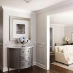 Chic foyer features upper walls painted pale gray and lower walls clad in light ...