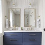 Deep blue painted cabinets in an otherwise all white bathroom. I also love the h...