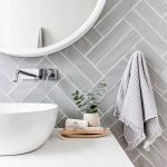 Grey herringbone tile bathroom wall