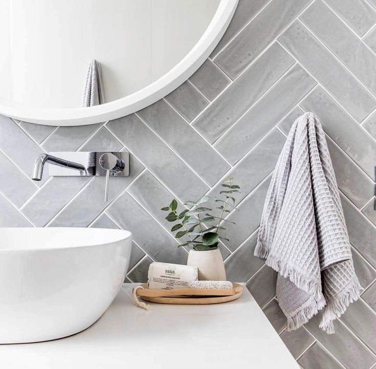 Grey herringbone tile bathroom wall