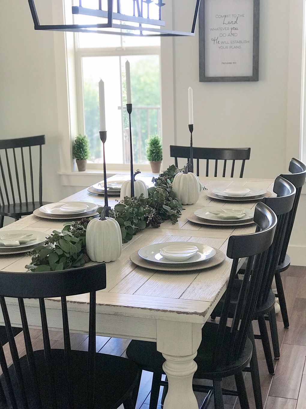 Simple and neutral thanksgiving tablescape with white dishes, black candlesticks…