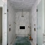 Stunning spa shower boasts white and gray marble tiles and ceiling fitted with a...