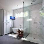 Transitional bathroom features a freestanding gray linen cabinet beside a tilted...