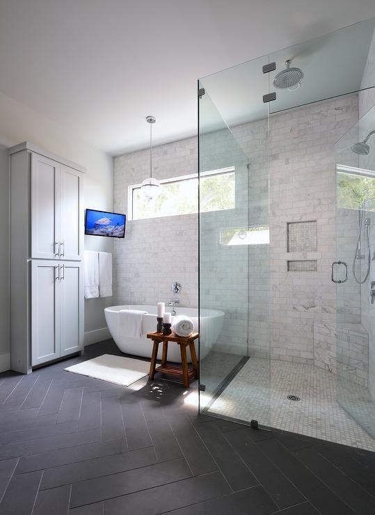 Transitional bathroom features a freestanding gray linen cabinet beside a tilted…