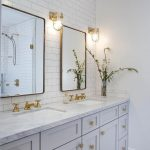 Well appointed light gray and white basement bathroom features two Restoration H...