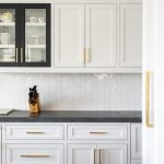 White shaker kitchen cabinets with various black frame cabinet doors accented wi...