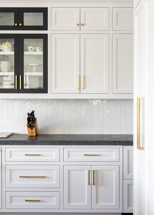 White shaker kitchen cabinets with various black frame cabinet doors accented wi…