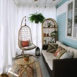 a small boho sunroom with a dark sofa, wicker furniture and a hanging chair plus...