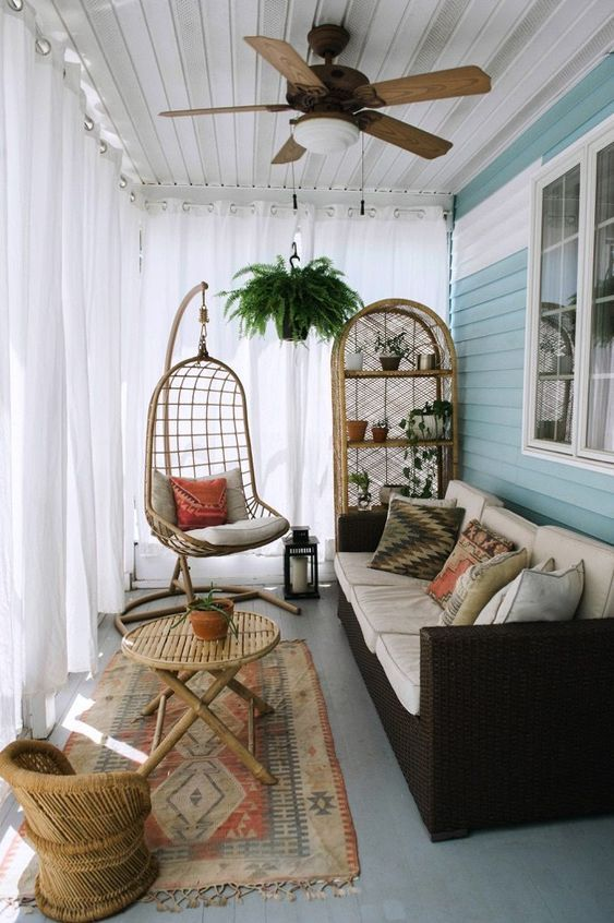 a small boho sunroom with a dark sofa, wicker furniture and a hanging chair plus…