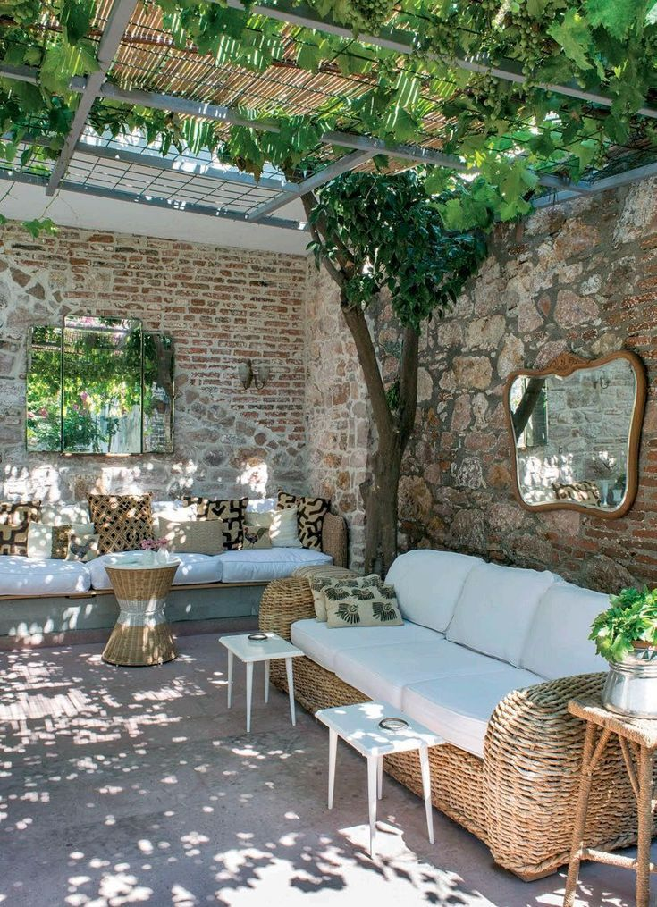 patio shaded with pergola covered in canvas, bamboo, and vines for filtered ligh…