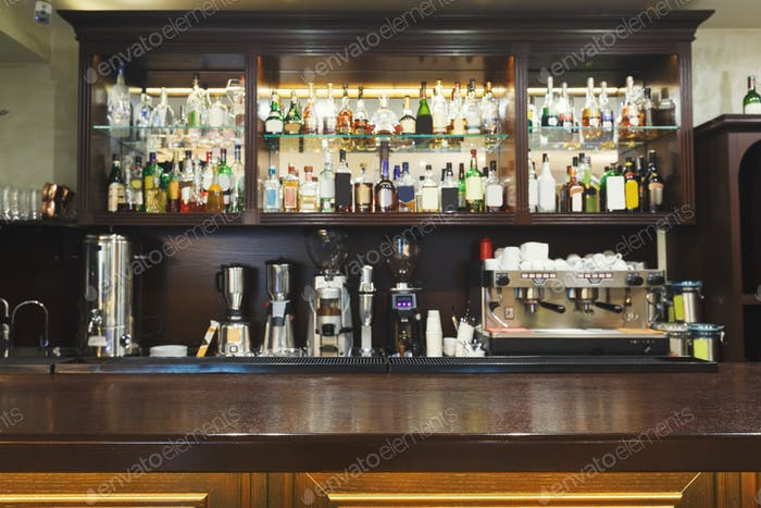 Bar counter with alcohol bottles assortment photo by Prostock .