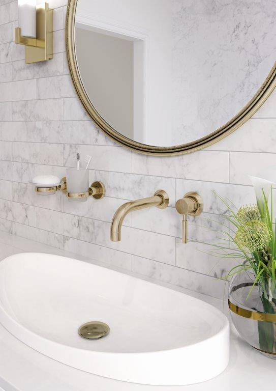 Gorgeous carrara marble bathroom with gold taps and accessories .