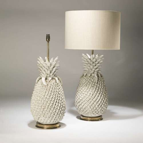 pair of large cream ceramic pineapple lamps on distressed brass .