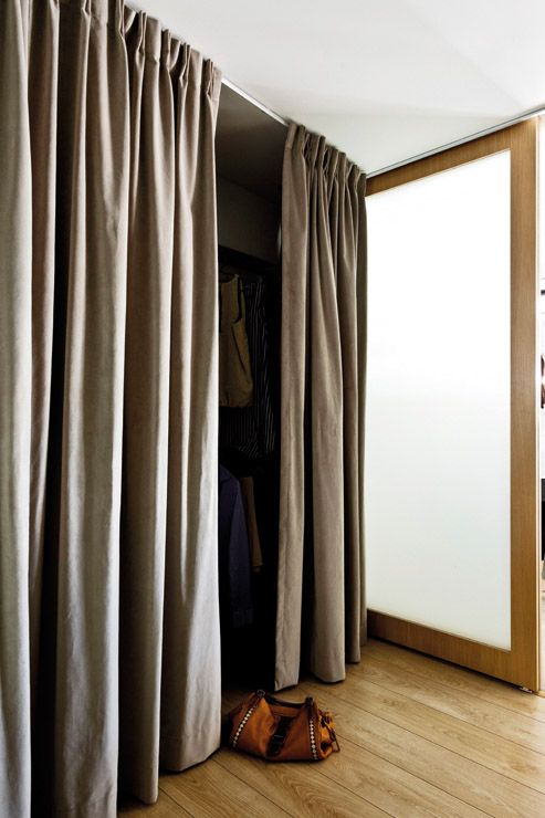 The walk-in wardrobe has a curtain 'door' to soften the look in .